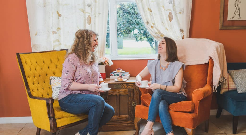 Empowered Princess Founders having tea and laughing in two princess chairs