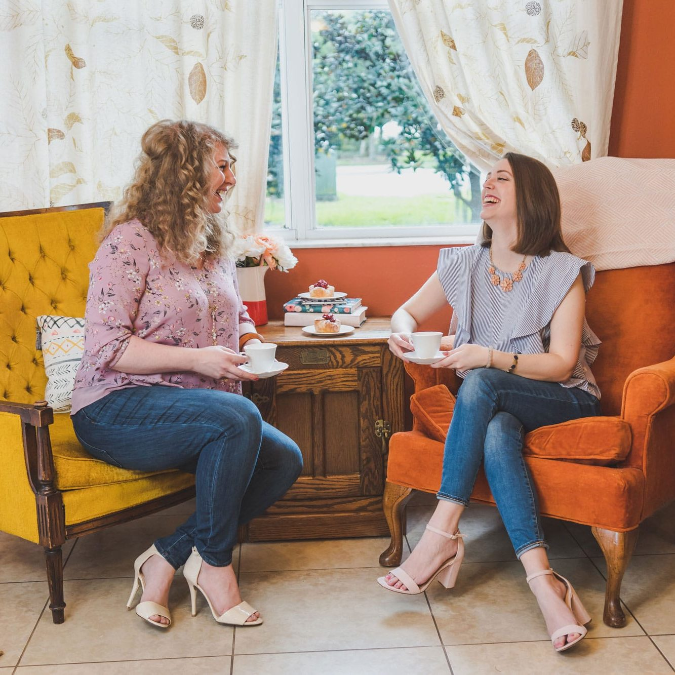 Empowered Princess founders laughing in chairs sharing a cup of tea and pastries